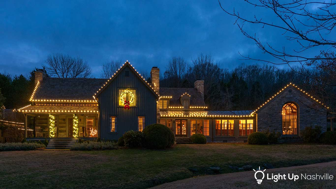 large home in Nashville with custom holiday lights on roofline and lit greenery