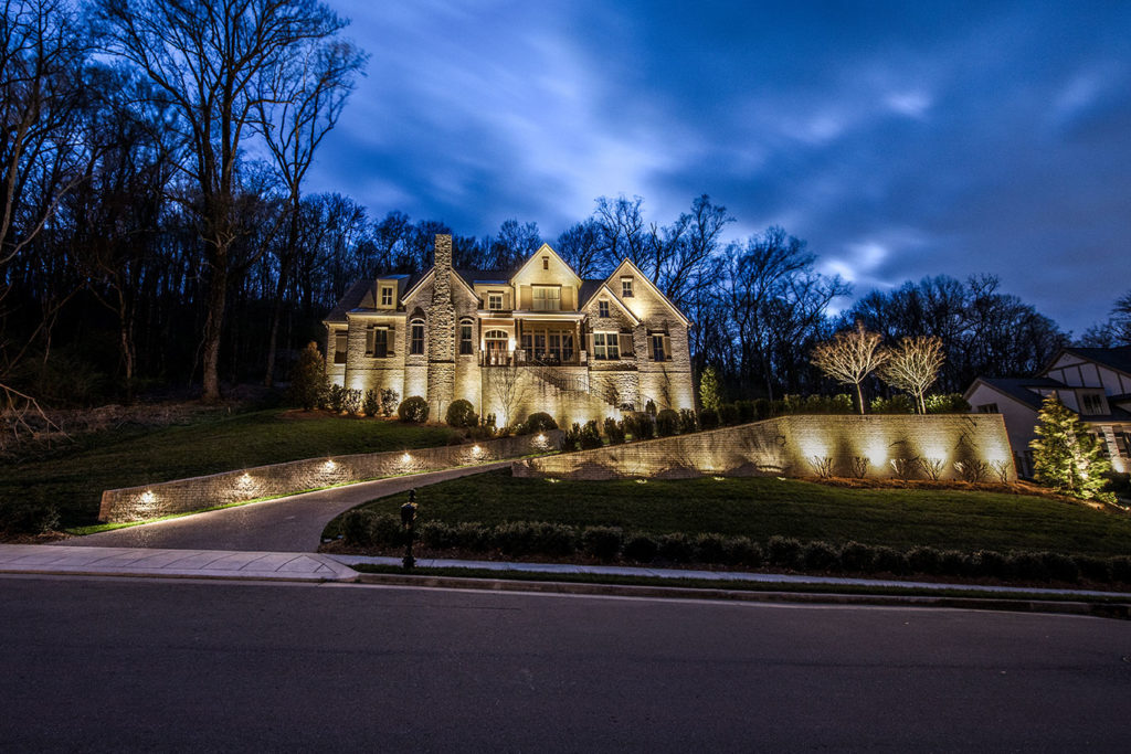 facade lighting on large white brick house